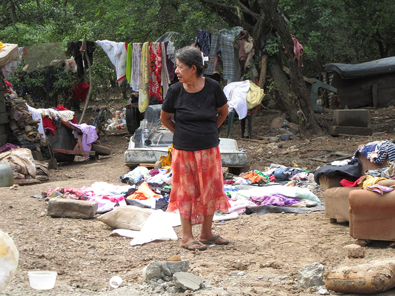 A Nicaraguan woman stands in her courtyard filled with items she rescued from her flooded home.