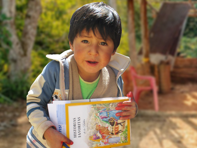 School boy in South America with a copy of CAM's Bible story book.