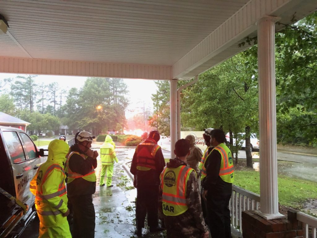 Search & Rescue team members prepare to move sixty elderly people from their housing complex to higher ground.